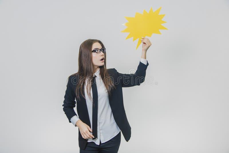 La jeune femme tient une bulle jaune de la parole, qui est en forme d'étoile, sur le fond blanc La jeune dame est photo libre de droits