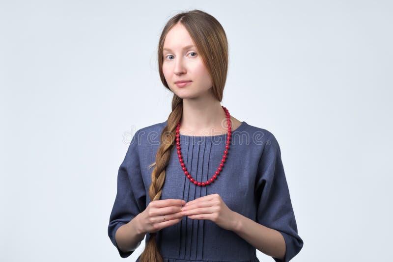 La jeune femme timide dans la robe bleue se sent maladroite image stock