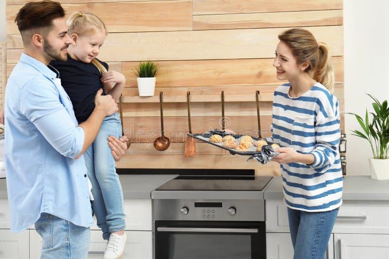 La jeune femme traitant sa famille avec le four fait maison a fait des biscuits cuire au four images stock