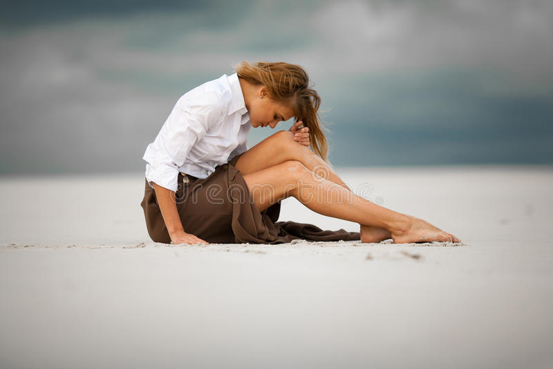 La jeune femme triste et songeuse s'assied sur le sable dans le désert image stock