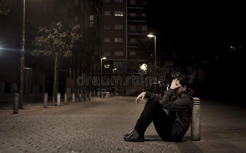 La jeune femme triste s'asseyant sur l'au sol de rue à la seule dépression de souffrance désespérée de nuit a laissé abandonné photo libre de droits