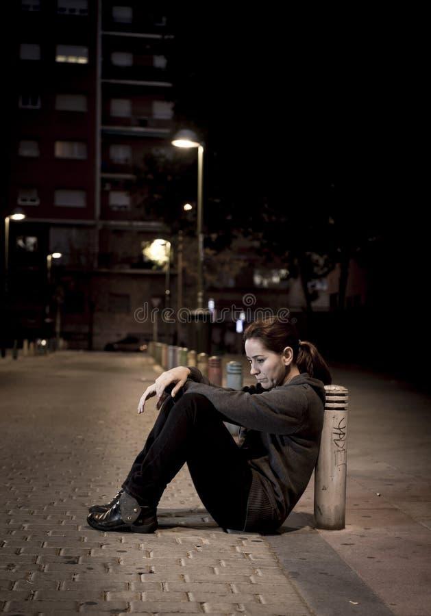 La jeune femme triste s'asseyant sur l'au sol de rue à la seule dépression de souffrance désespérée de nuit a laissé abandonné image libre de droits
