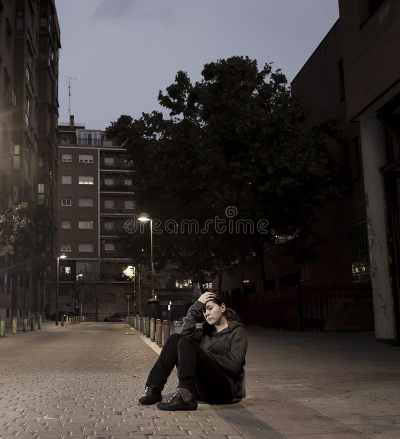 La jeune femme triste s'asseyant sur la rue a rectifié à seul désespéré de nuit photographie stock