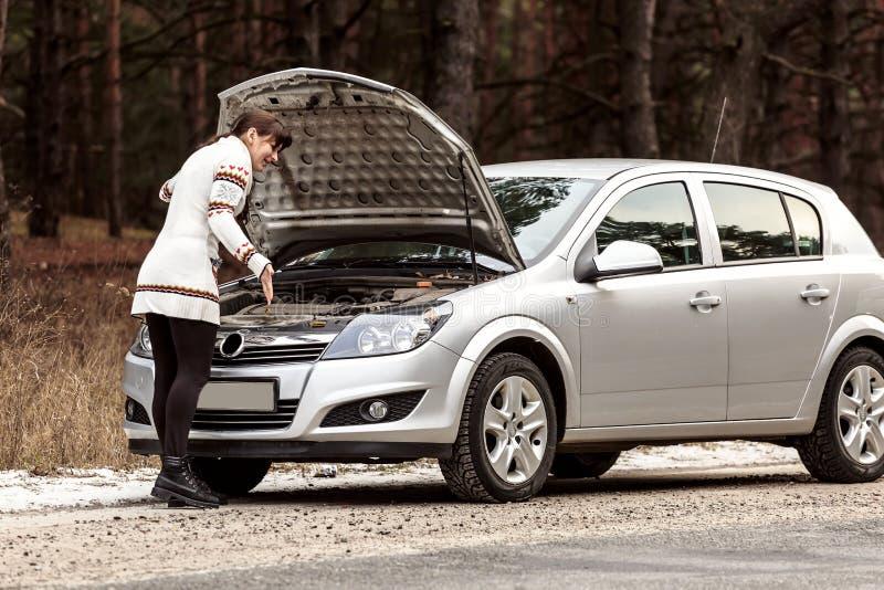 La jeune femme a un problème avec sa voiture sur la route photographie stock