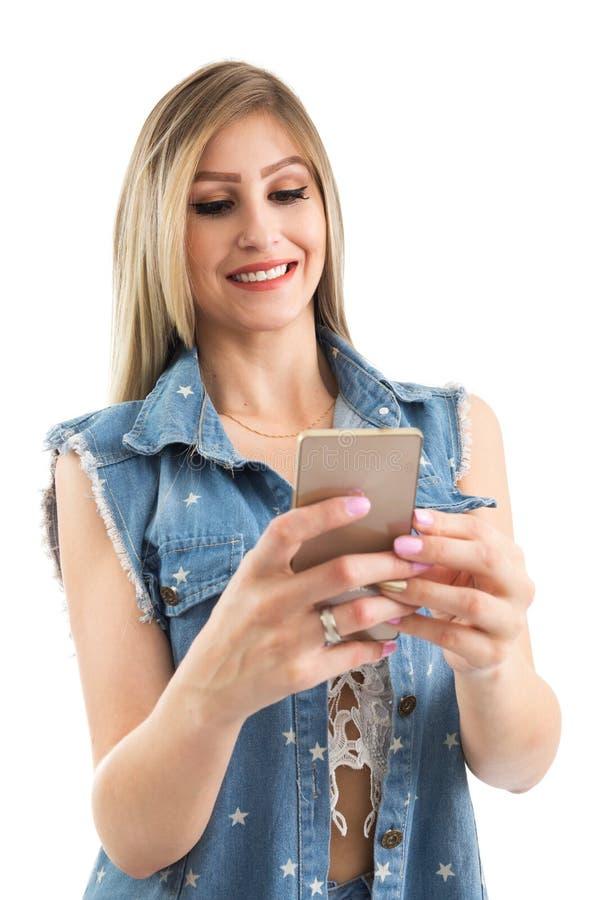 La jeune femme utilise le téléphone portable Gilet de port de jeans de personne blonde image libre de droits