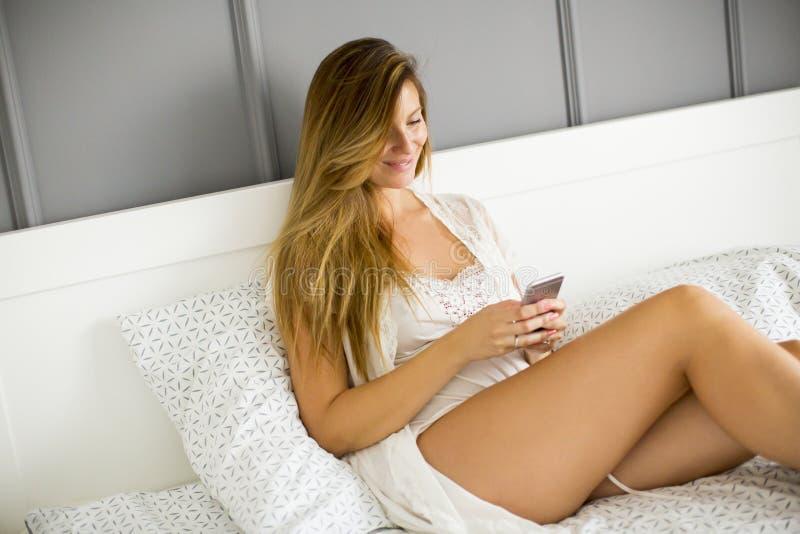 La jeune femme utilise un téléphone portable sur le lit photo libre de droits