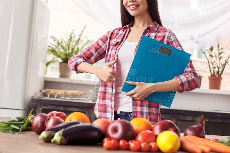 La jeune fille à la position saine de mode de vie de cuisine près de la participation de table mesure le thub de représentation g image libre de droits