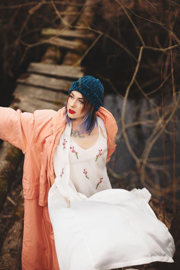 La jeune fille élégante marche le long de la rivière, près d'un petit pont en bois photographie stock