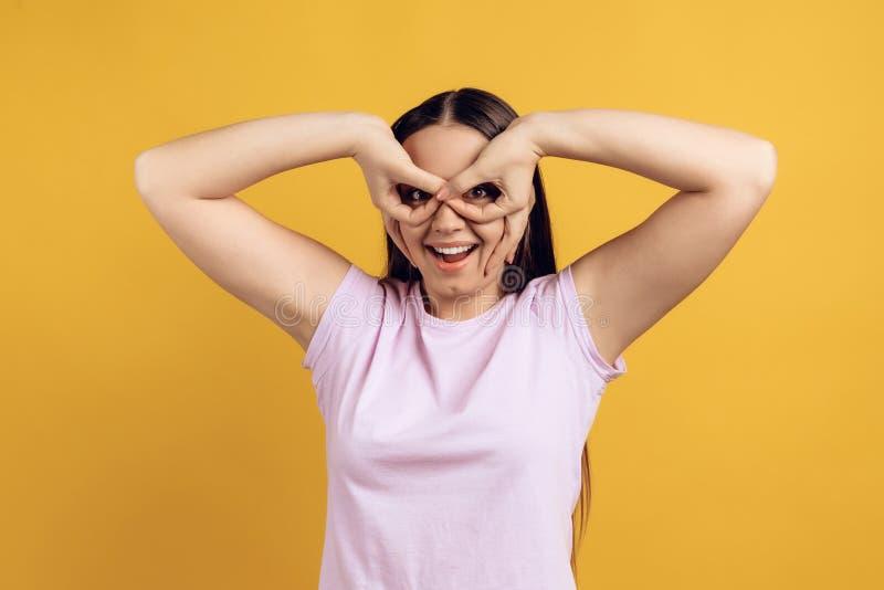 La jeune fille énergique couvre des yeux de mains images libres de droits