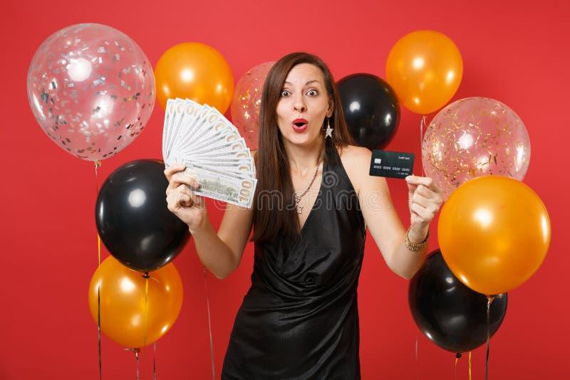 La jeune fille étonnée dans la robe noire célébrant un bon nombre de paquet de carte de crédit de prise de dollars encaissent l'a photos libres de droits
