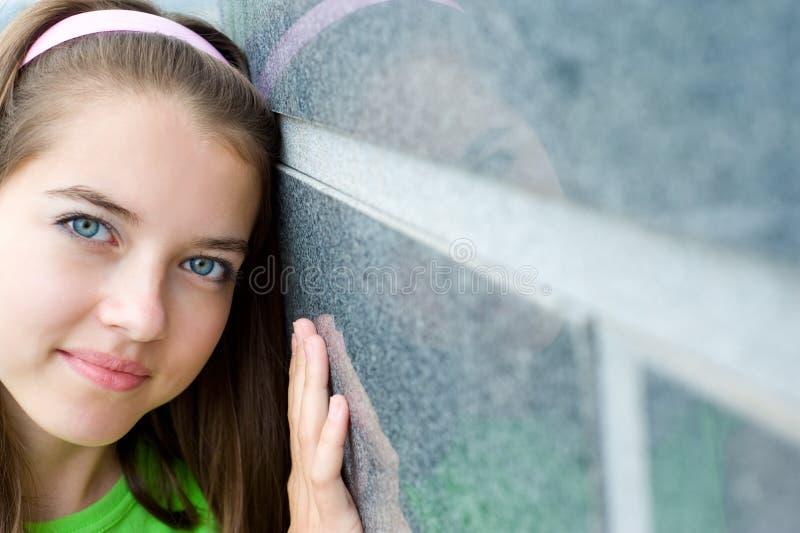 La jeune fille étreint le mur image stock