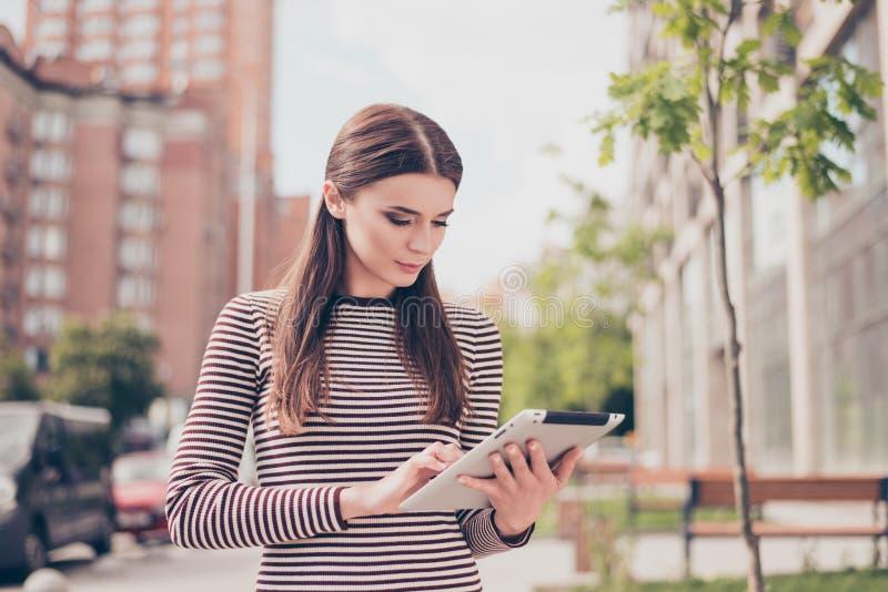 La jeune fille étudie au printemps le parc dehors, passant en revue sur h photo stock
