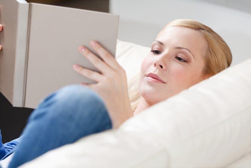 La jeune fille affiche le livre se trouvant sur le sofa photographie stock libre de droits