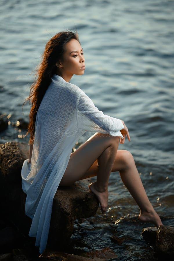 La jeune fille asiatique dans le maillot de bain et la longue chemise détendent sur le bord de la mer au coucher du soleil image libre de droits
