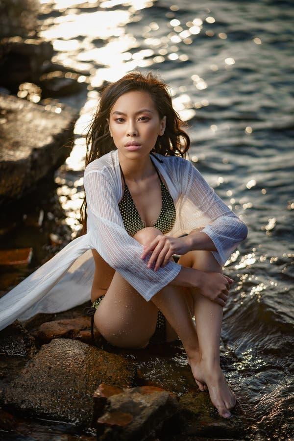 La jeune fille asiatique dans le maillot de bain et la longue chemise détendent sur le bord de la mer au coucher du soleil photo libre de droits