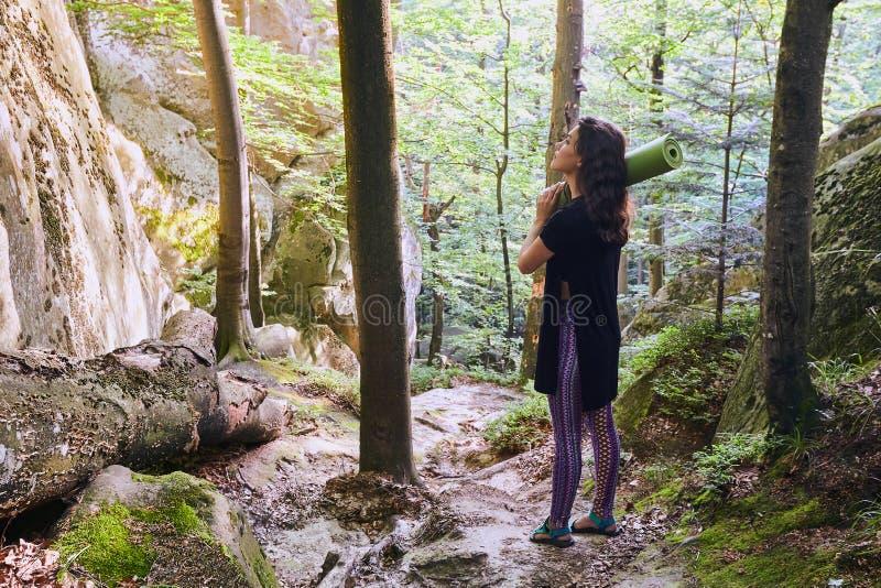 La jeune fille attirante dans la for?t de montagne dans la lumi?re du soleil tient un tapis de yoga photographie stock libre de droits