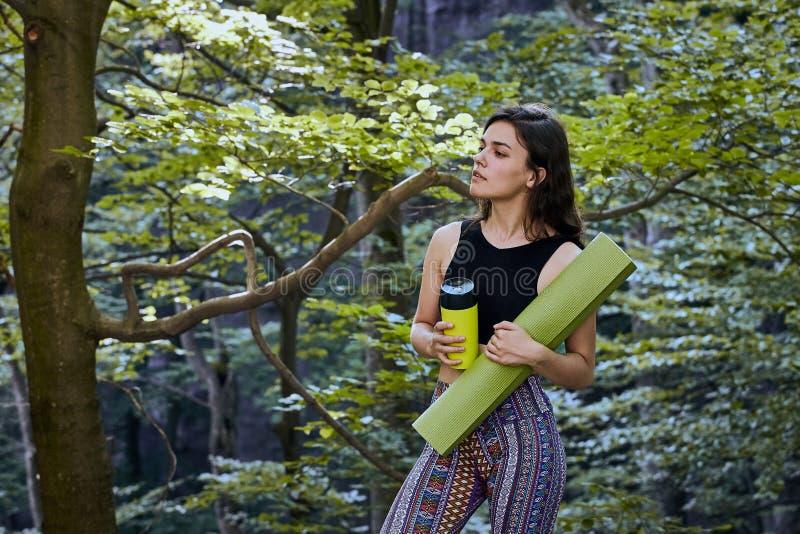 La jeune fille attirante dans la for?t tient un tapis de yoga et une tasse image stock