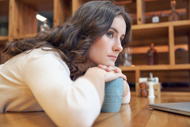 La jeune fille aux cheveux longs attirante avec un visage ennuyeux plié à la table en café et examine pensivement la distance photos stock