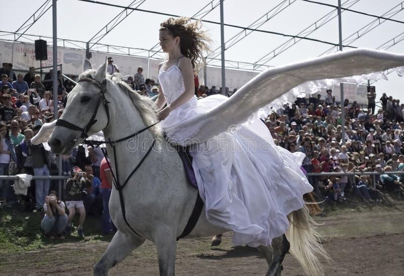 La jeune fille avec de grandes ailes derrière elle de retour monte sur un cheval blanc photo libre de droits