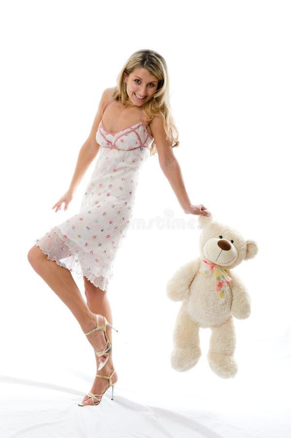 La jeune fille avec du charme joue avec un ours images stock