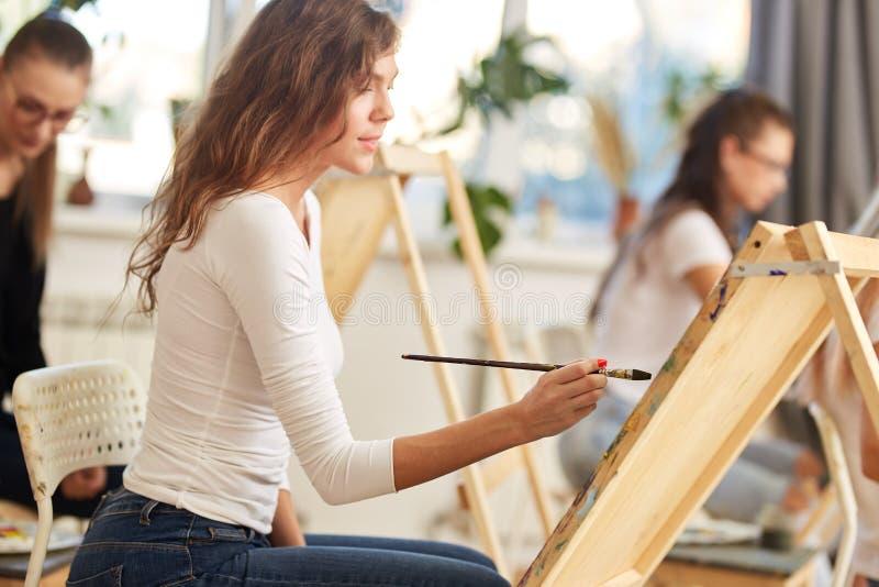 La jeune fille avec du charme avec les cheveux boucl?s bruns habill?s dans le chemisier blanc peint un tableau au chevalet dans l images stock