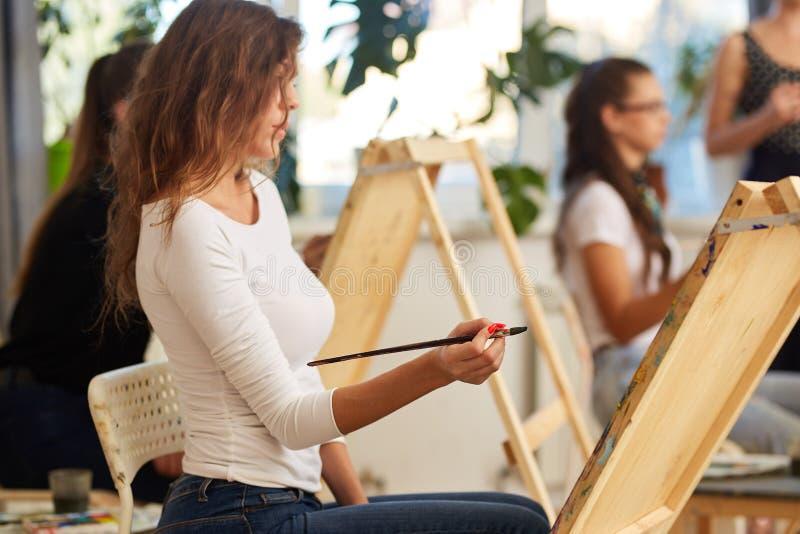 La jeune fille avec du charme avec les cheveux boucl?s bruns habill?s dans le chemisier blanc peint un tableau au chevalet dans l images libres de droits