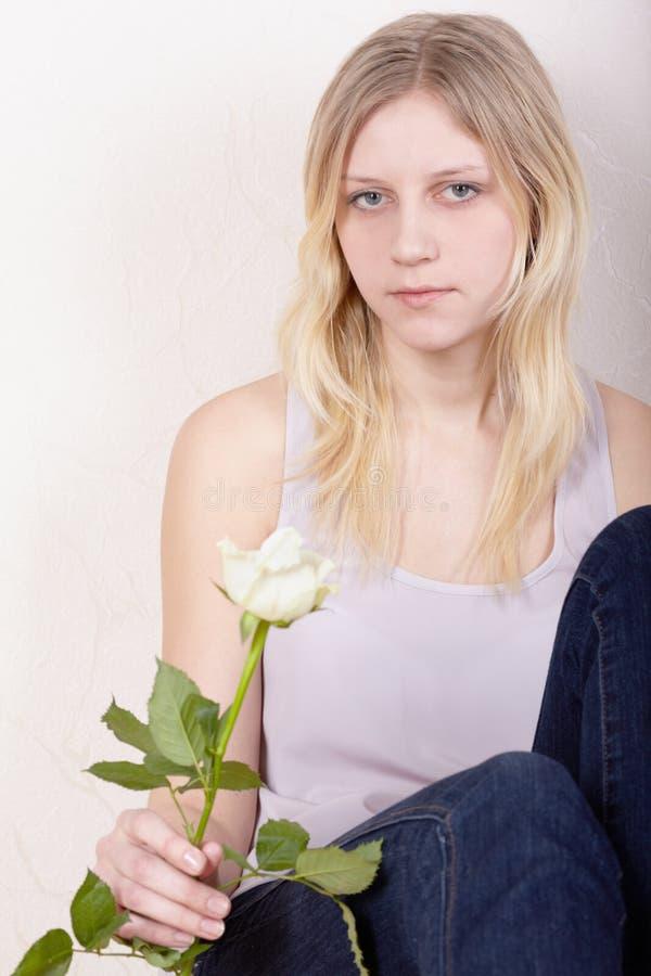 La jeune fille avec la rose s'assied calmement image libre de droits