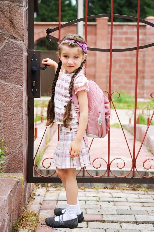 La jeune fille avec le bagpack rose part pour l'école photos stock