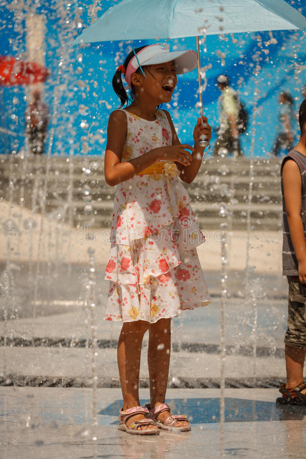 La jeune fille avec le parapluie rit de l'eau de pulvérisation image libre de droits