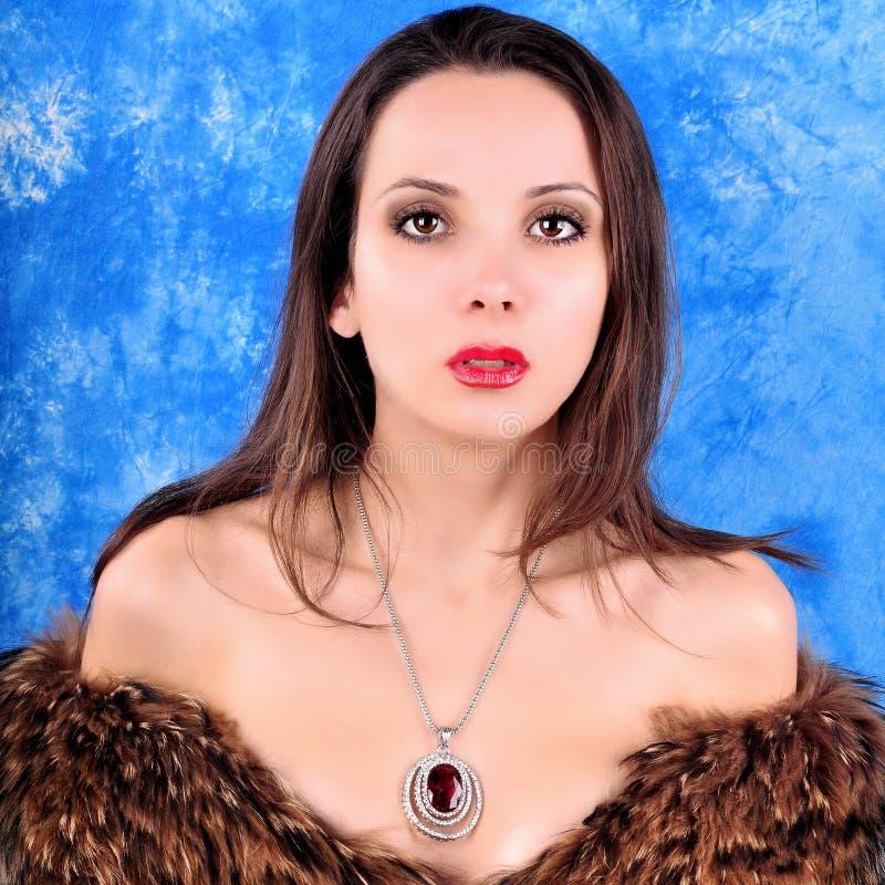 La jeune fille avec un pendant s'est habillée dans un manteau de fourrure photo stock