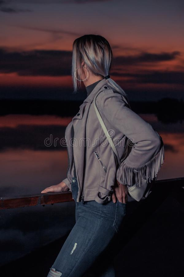 La jeune fille avec un sac à dos se tient à côté de à une barrière en bois à s photos libres de droits