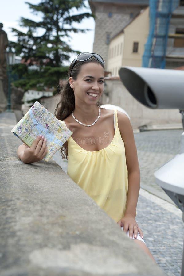 La jeune fille avec une carte dans les mains et un v jaune image stock