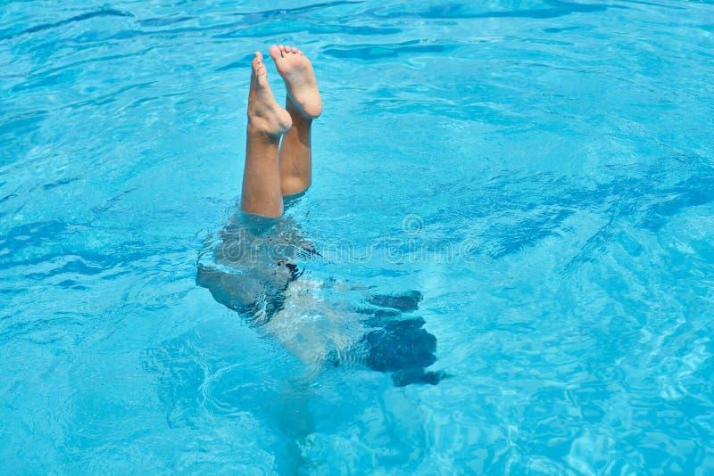 La jeune fille blanche avec le bikini noir et blanc fait le saut périlleux dans l'eau de la piscine photos stock
