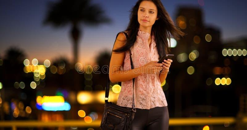 La jeune fille blanche utilise son téléphone tandis que sur la ville images libres de droits