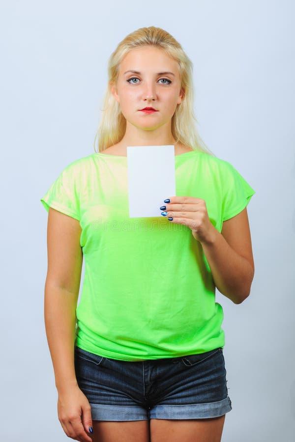 La jeune fille blonde tient la carte de visite professionnelle de visite image libre de droits