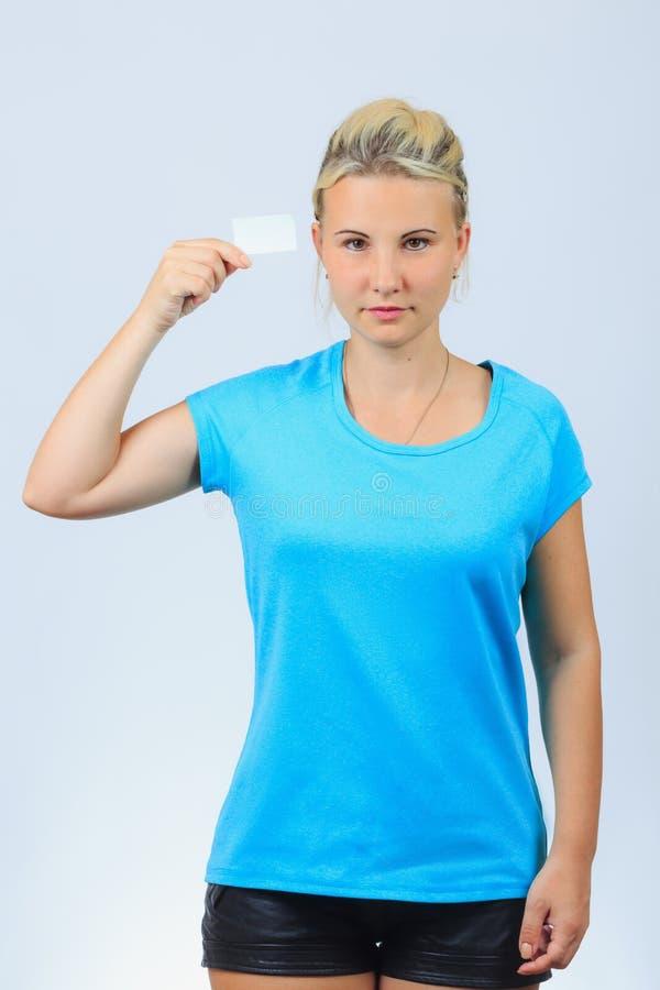 La jeune fille blonde tient la carte de visite professionnelle de visite photographie stock