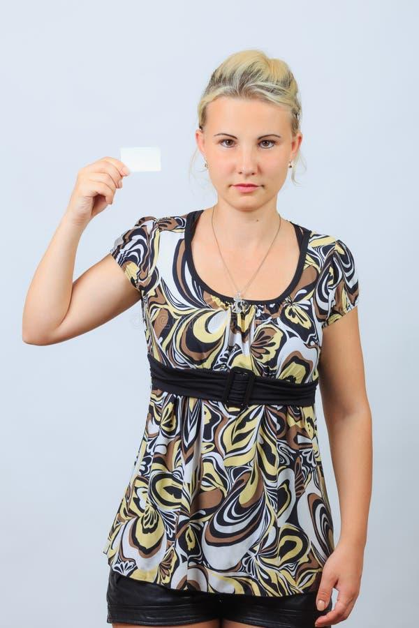 La jeune fille blonde tient la carte de visite professionnelle de visite photos libres de droits
