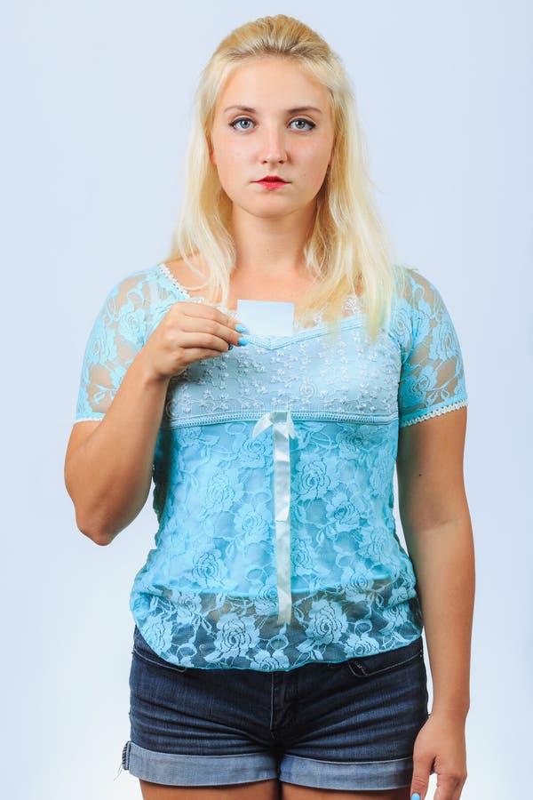 La jeune fille blonde tient la carte de visite professionnelle de visite photos stock