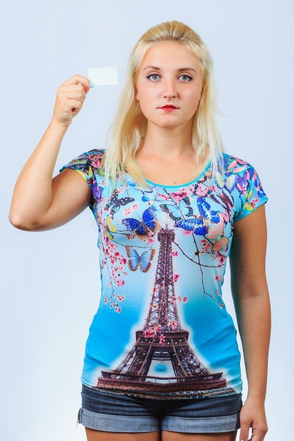 La jeune fille blonde tient la carte de visite professionnelle de visite photo stock