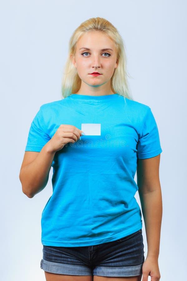La jeune fille blonde tient la carte de visite professionnelle de visite photographie stock libre de droits