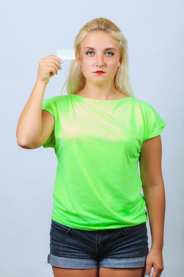 La jeune fille blonde tient la carte de visite professionnelle de visite images stock