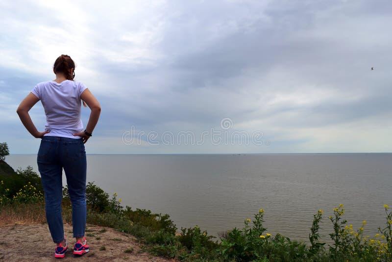 La jeune fille bouclée blonde regardant le soleil flou par une brume épaisse sur une mer calme et les cieux bleus de retour regar photo libre de droits