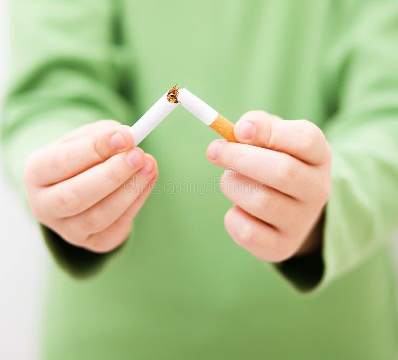 La jeune fille casse une cigarette photographie stock libre de droits
