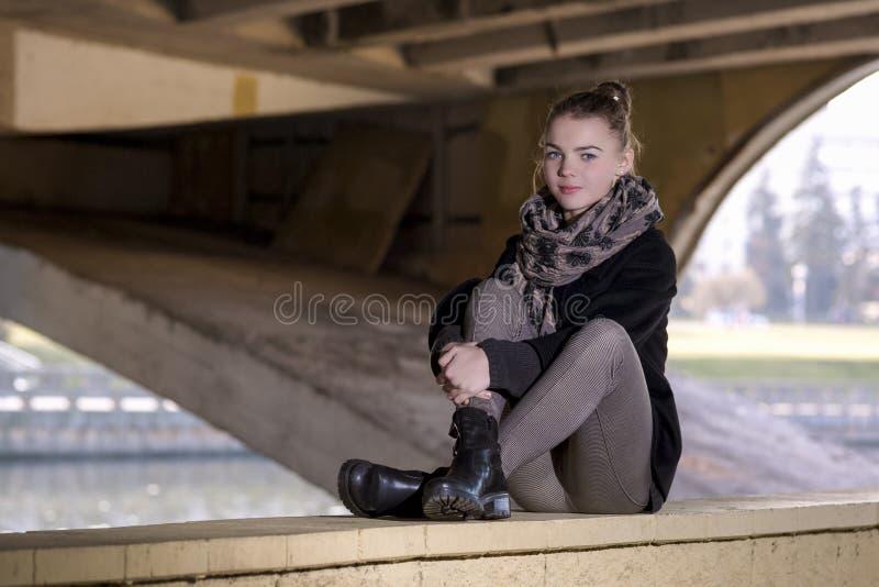 La jeune fille caucasienne d'adolescent s'asseyant avec ses jambes pliées se surpassent photographie stock libre de droits