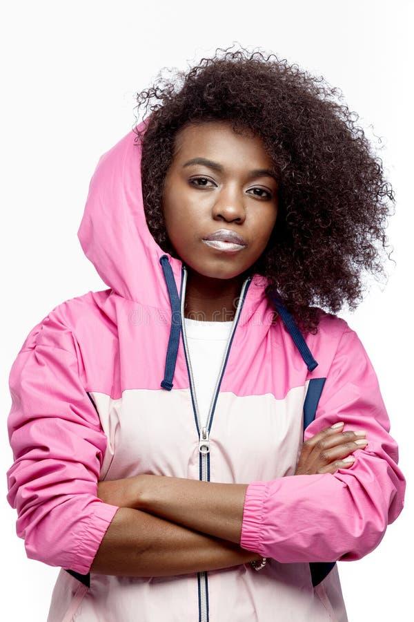 La jeune fille châtain bouclée de mod habillée dans la veste de sports à capuchon rose pose au fond blanc dans le studio photographie stock