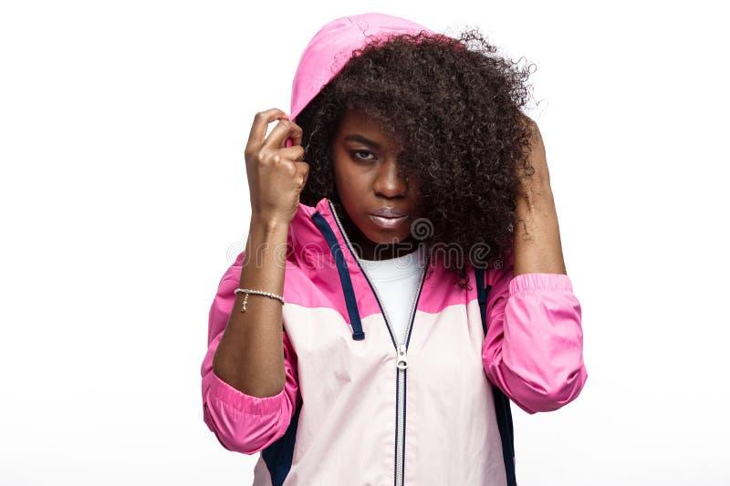 La jeune fille châtain bouclée de mod habillée dans la veste de sports à capuchon rose pose au fond blanc dans le studio image libre de droits
