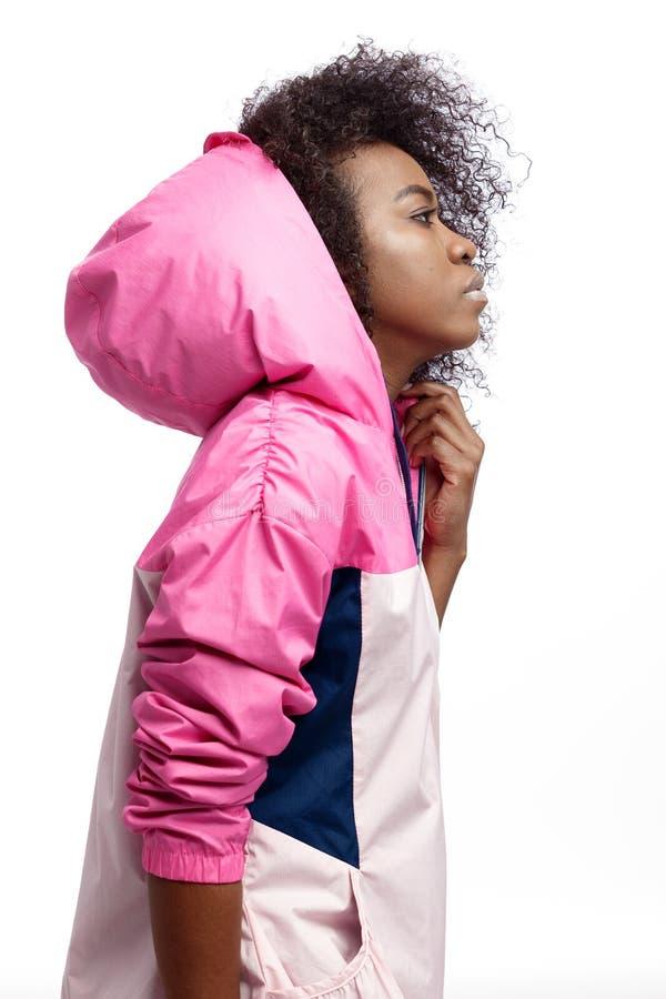 La jeune fille châtain bouclée de mod habillée dans la veste de sports à capuchon rose pose au fond blanc dans le studio images libres de droits
