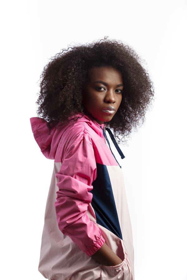 La jeune fille châtain bouclée habillée dans la veste de sport rose se tient au fond blanc dans le studio photo stock