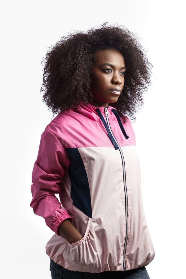 La jeune fille châtain bouclée habillée dans la veste de sport rose se tient au fond blanc dans le studio images stock