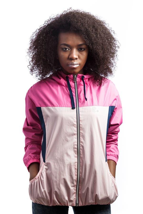 La jeune fille châtain bouclée habillée dans la veste de sport rose se tient au fond blanc dans le studio photo libre de droits